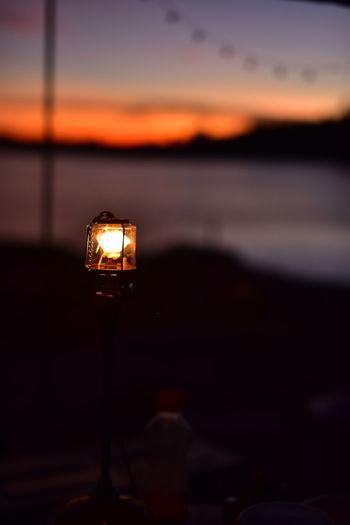 Close-up of illuminated lamp against sky at sunset