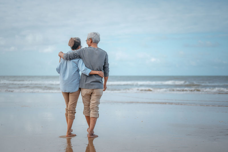 Rear view of couple walking on shore at beach