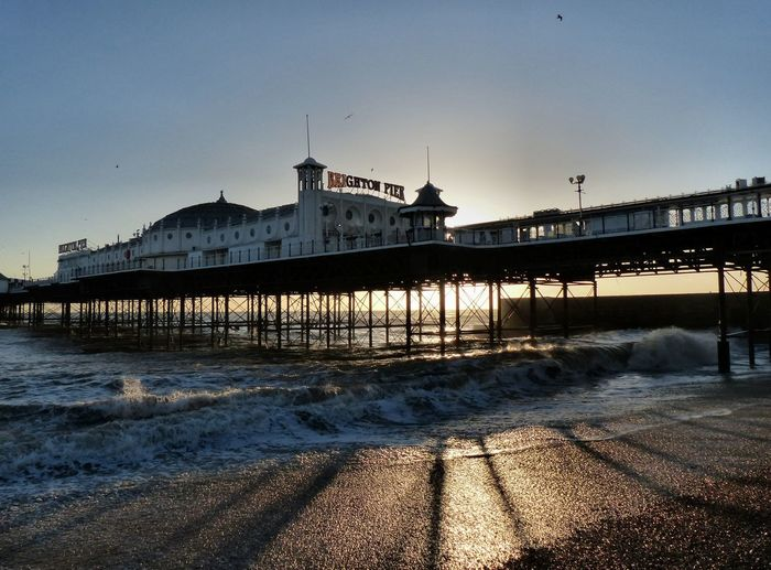 Pier in sea at sunset