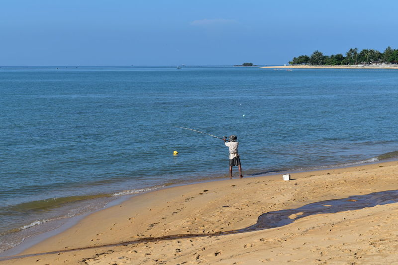 native fisherman on thai island of Ko Samui Fishing Rod Sky And Sand Alone At The Beach Beach Beachphotography Beauty In Nature Catching Fish Craft Craftmanship Exotic Beach Fisherman Horizon Over Water Land One Person Outdoors Real People Rear View Sand Sea Water