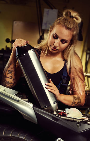 Young woman holding exhaust pipe in motorcycle while standing at workshop