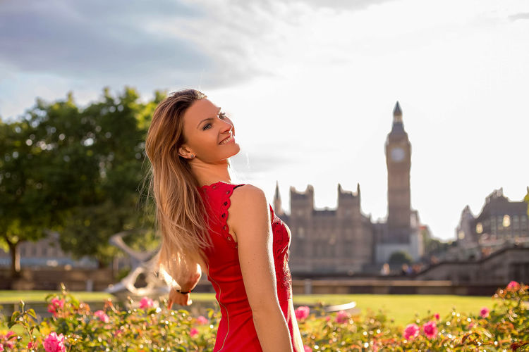 Smiling young woman standing against big ben