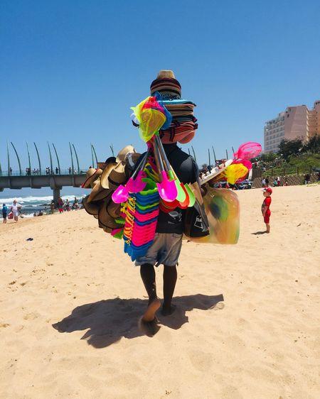 Woman with umbrella on beach against clear sky