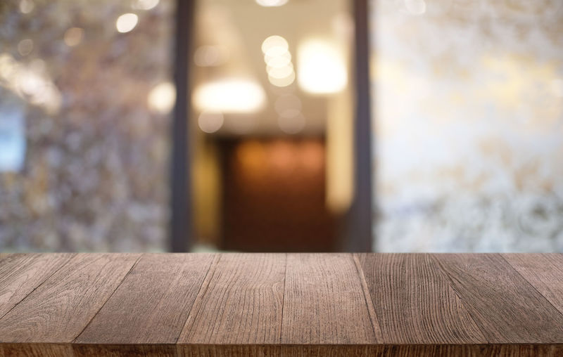 Close-up of wooden table with open door in background