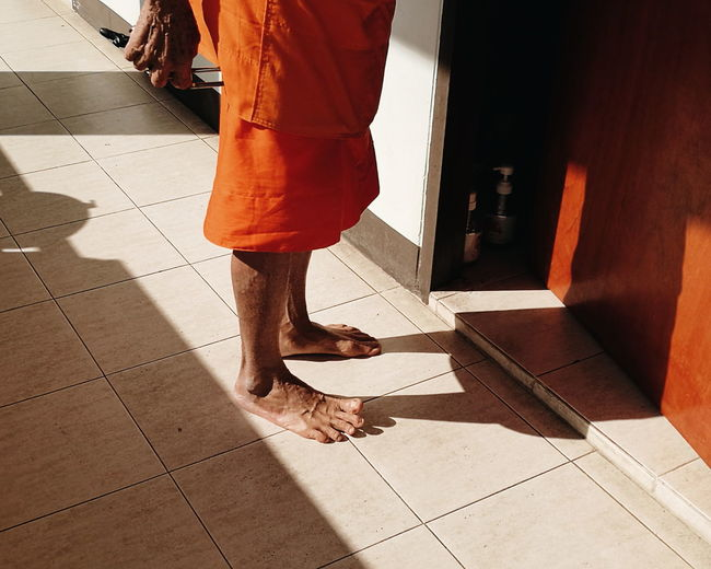 Low section of monk standing by door on tiled floor