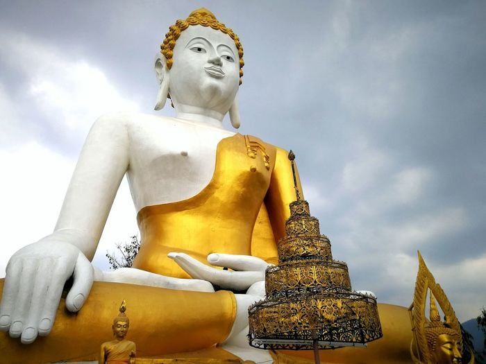 Low angle view of large buddha statue against cloudy sky