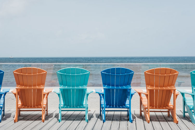 Empty chairs at beach against sky