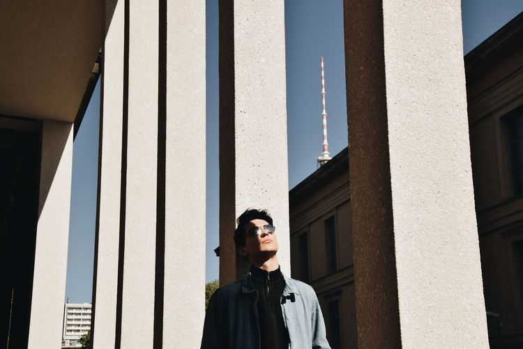 Low angle view of young man looking away against building