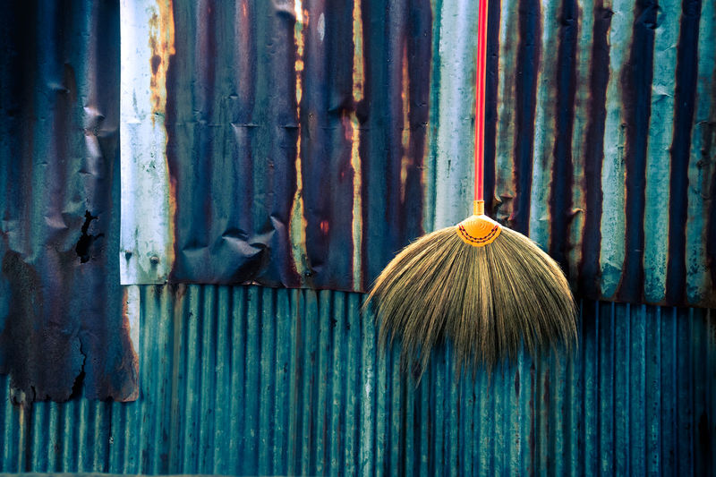 Broom hanging by rusty metal fence