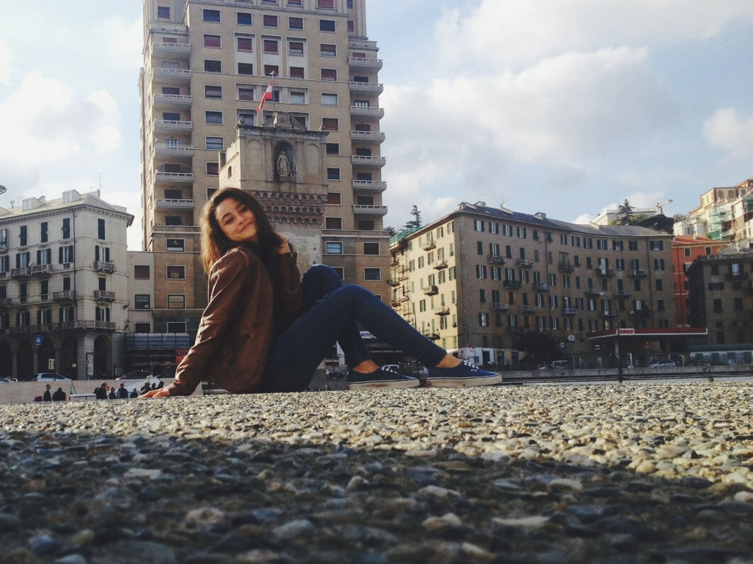 building exterior, architecture, built structure, lifestyles, sky, young adult, leisure activity, city, casual clothing, street, cloud - sky, sitting, full length, person, city life, sunglasses, day, young women