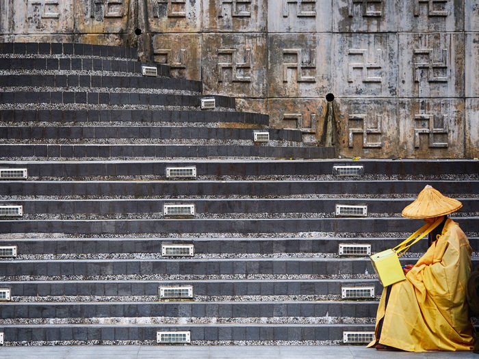 Side View Of Monk Sitting On Temple Steps
