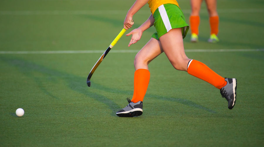 Young hockey player woman with ball in attack playing field hockey game Field Field Hockey Review Field Hockey Fight Grass Green Color Active Athlete Ball Body Part Day Focus On Foreground Green Color Healthy Lifestyle Human Leg Leisure Activity Lifestyles Low Section Motion One Person Orange Color Playing Real People Skill  Sport Sports Stick Team Women