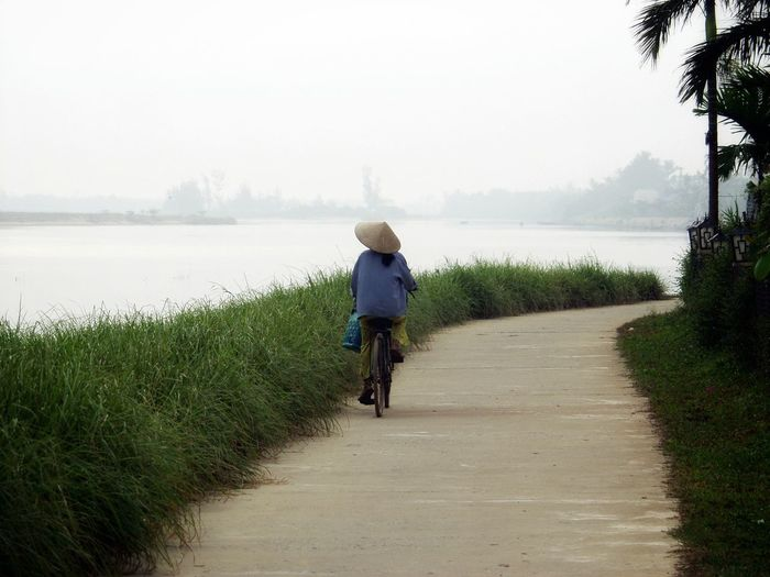 Women Riding A Bicycle Rear View One Woman Only Vitenam Traditional Culture Traditional Clothing Culture Nature_collection Beauty In Nature Outdoors Local Road River View River Views Hanoi, Vietnam