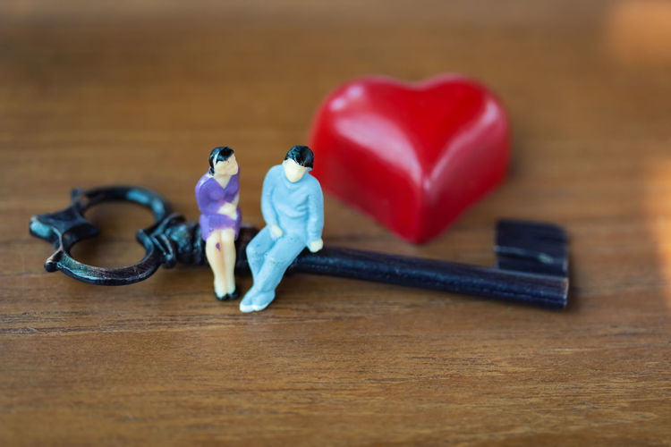 High angle view of figurines sitting on key with heart shape at wooden table