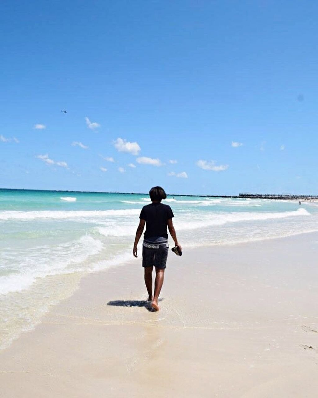 sea, beach, full length, horizon over water, rear view, nature, one person, sky, beauty in nature, scenics, sand, water, day, tranquility, vacations, standing, outdoors, wave, blue, ankle deep in water, real people, young adult, one man only, adult, adults only, people