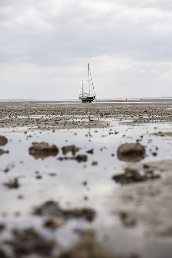 Sailboat on sea shore against sky