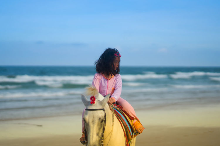 Rear view of girl riding on horse ft at beach against sky