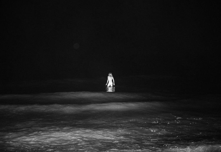 Rear view of person standing in water at night