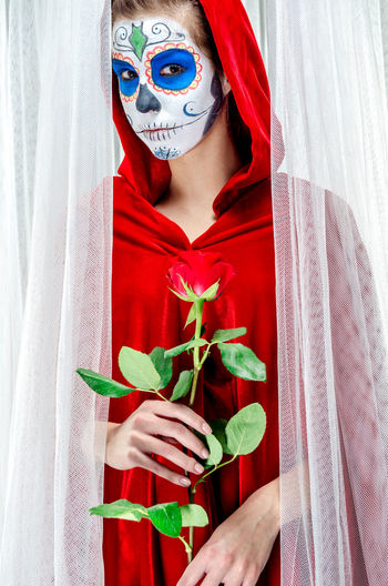 Day of the dead girl with sugar skull make-up Day Of The Dead Death Halloween Horror Makeup Mexican Culture Mortality Woman Body Arts Curtain Day Of The Dead Skull Face Paint Female Flower Girl Holding Hood Macabre Art Mexican Holidays One Person Red Rose Skeleton Makeup Sugar Skull Voodoo Young Adult