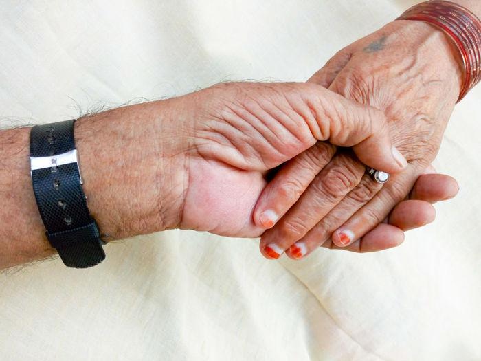 Cropped Image Of Senior Couple Holding Hands