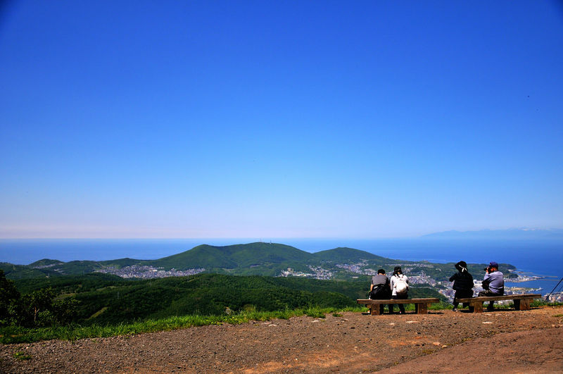 People Sitting On Mountain Against Clear Blue Sky