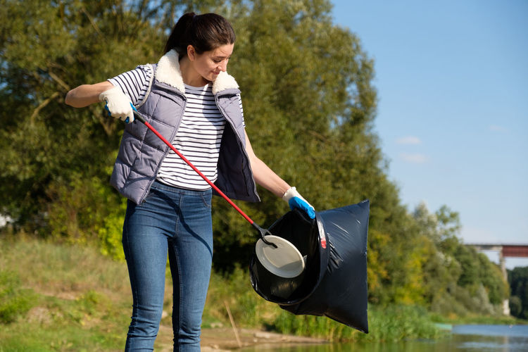 Young woman putting garbage in plastic