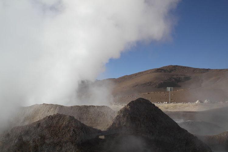 Steam emitting from geyser against sky