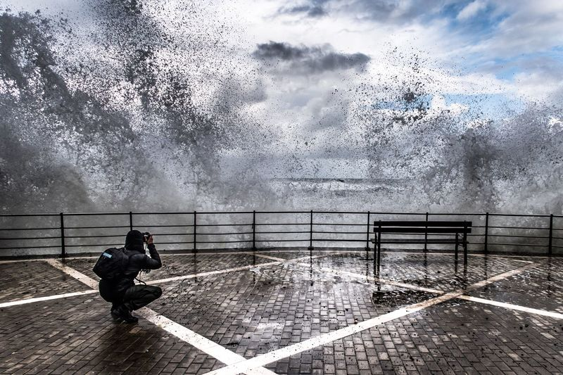 Man photographing splashing waves while crouching on promenade against sky