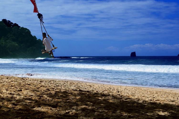 Man swinging at beach against sky