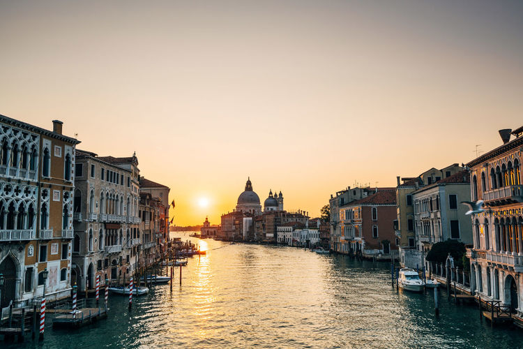 Grand Canal And Santa Maria Della Salute Against Sky In City During Sunset