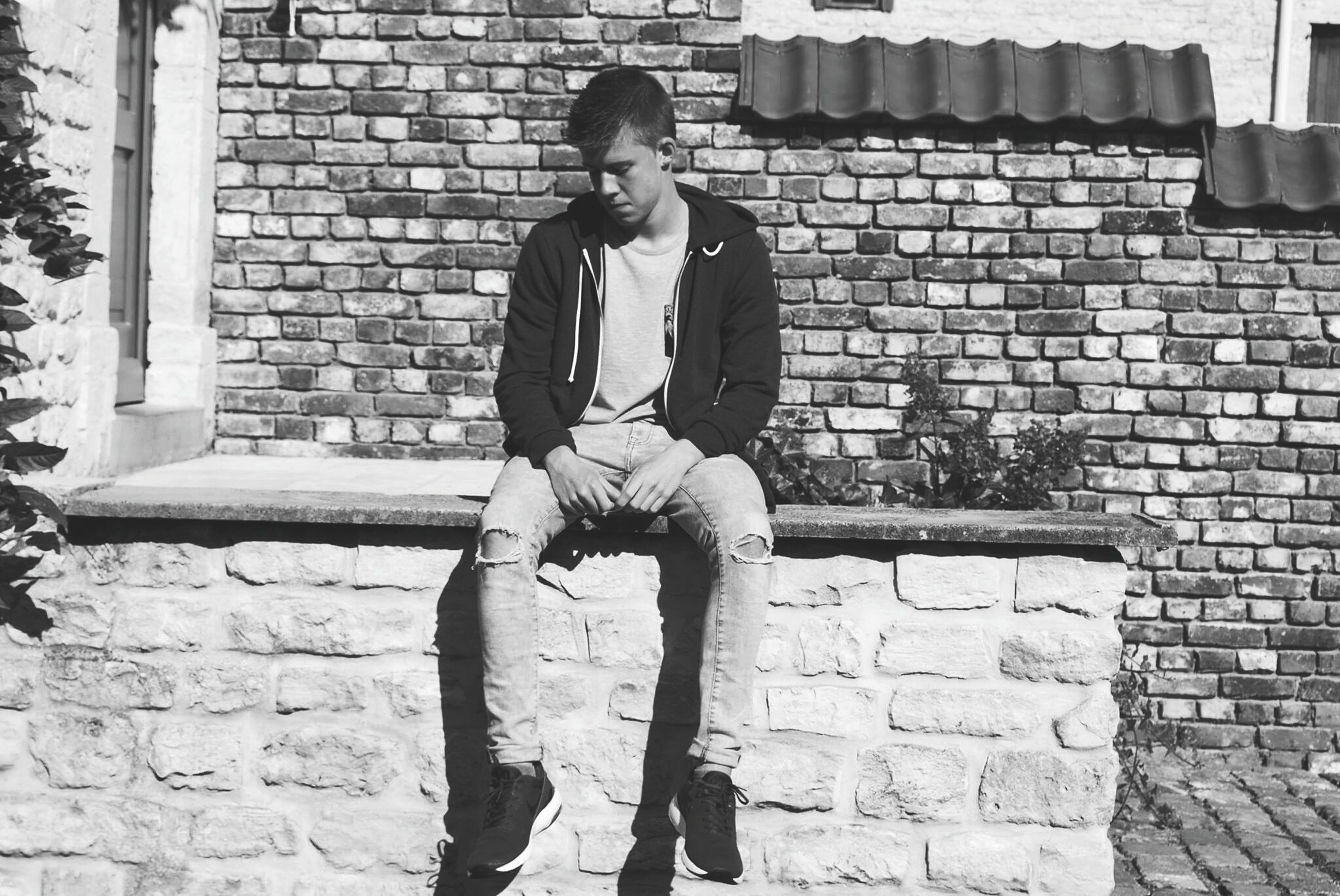 building exterior, casual clothing, person, architecture, built structure, lifestyles, brick wall, young adult, full length, leisure activity, front view, standing, wall - building feature, looking at camera, young men, portrait, three quarter length