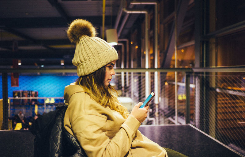 Adult Airport City Communication Girl Holding Indoors  Knit Hat Leica Leisure Activity Lifestyles Mobile Phone Night Nightlife One Person People Portable Information Device Ryanair Smart Phone Technology Text Messaging VSCO Warm Clothing Wireless Technology Young Adult