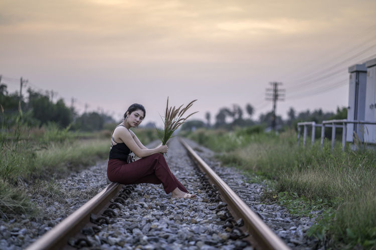 Portrait of woman holding plant while sitting on railroad track during sunset