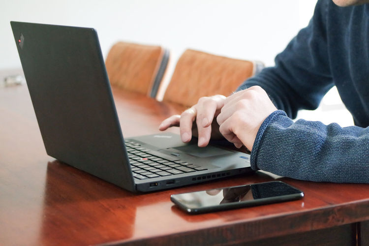 Laptop Technology Wireless Technology Computer Using Laptop Communication One Person Table Real People Connection Indoors  Human Hand Hand Businessman Business Person Meeting Working Day Education Business Stories Business Strategy Going Remote Desktop