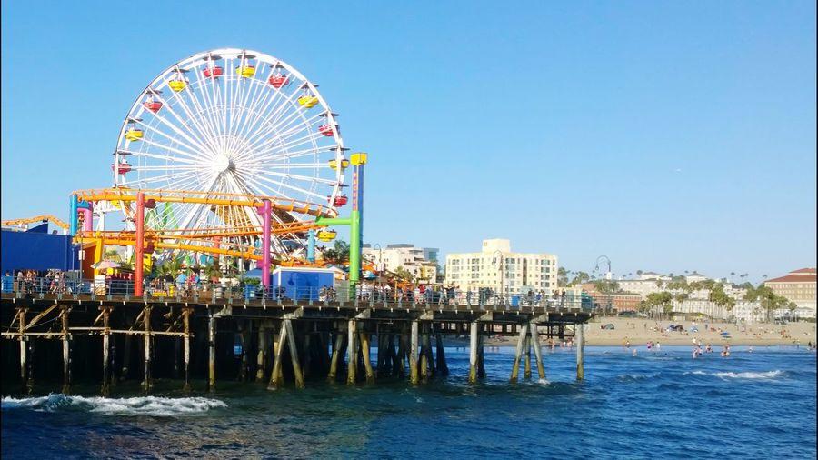 Ferris Wheel On Pier Over Sea Against Clear Blue Sky