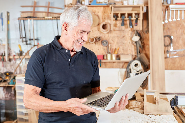 Smiling man with laptop in workshop