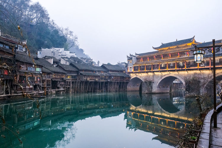 The river side in the evening at Fenghuang, China. Architecture Built Structure Water Reflection Building Exterior Sky Nature Waterfront Building Day Lake Travel Destinations Travel Clear Sky Tree Incidental People Old Arch Bridge China