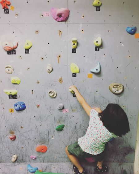 Rear view of girl climbing on wall