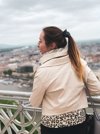 Rear view of woman looking away while standing by railing against sky