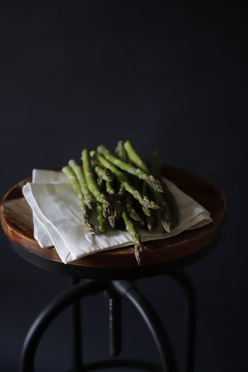 Close-up of salad in plate on table against black background