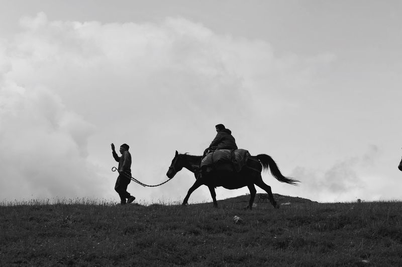Low angle view of man walking by woman riding horse on land