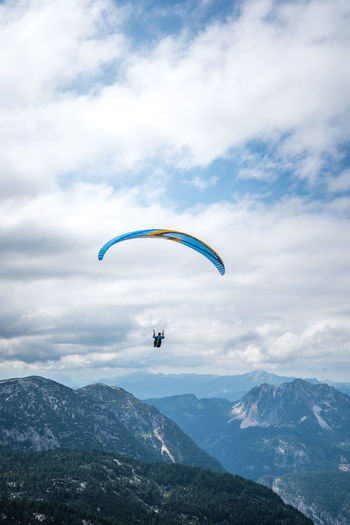 Man paragliding against Alps Copy Space RISK Adventure Beauty In Nature Cloud - Sky Day Extreme Sports Leisure Activity Lifestyles Low Angle View Men Mid-air Mountain Mountain Range Mountains Nature One Person Outdoors Parachute Paragliding People Real People Scenics Sky Tranquility