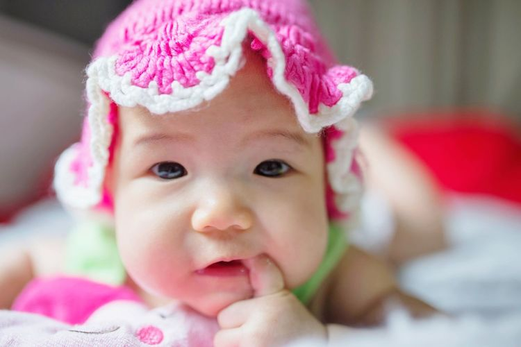 Portrait of cute baby girl with finger in mouth