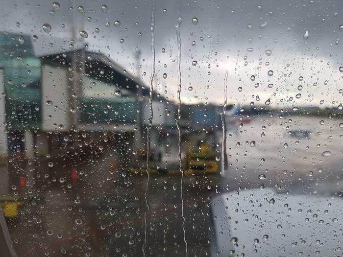 Buildings against cloudy sky seen through wet window