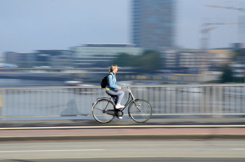 Blurred motion of woman riding bicycle on road in city