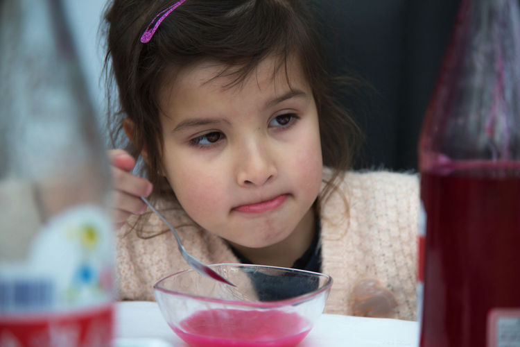Close-up of girl with juice served in bowl on table
