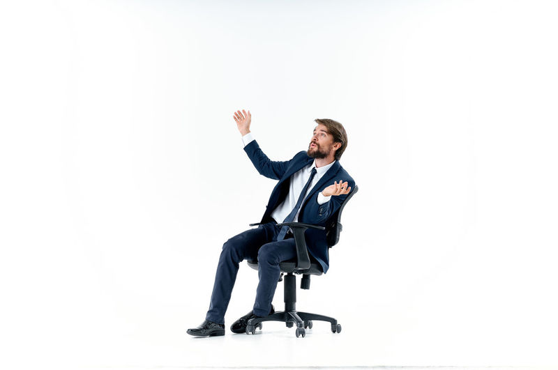 Man sitting on chair against white background