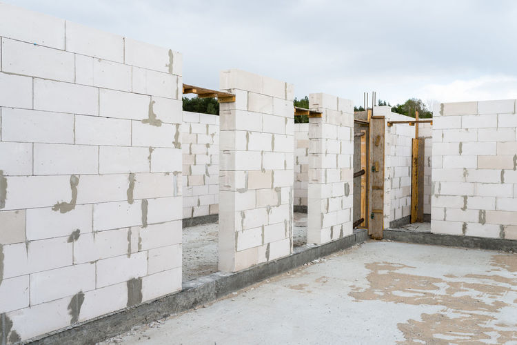 The walls of a house built of white brick with reinforced concrete pillars at the end of which