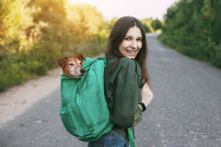 A smiling girl is holding a green backpack on her shoulder, from which a cute dog looks out