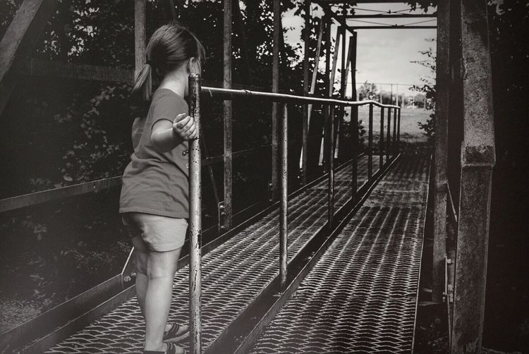 Rear view of girl standing on footbridge